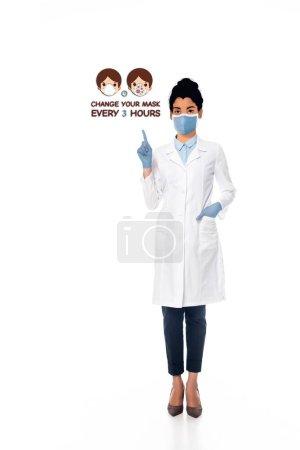 Photo pour Médecin afro-américain avec visage illustré en masque médical pointant du doigt changer votre masque toutes les 3 heures illustration sur blanc - image libre de droit