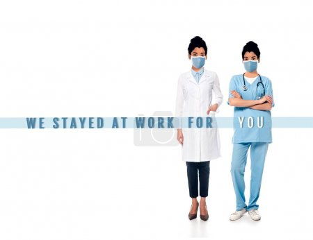 Photo for African american nurse and doctor with illustrated faces in medical masks on white, we stayed at work for you lettering - Royalty Free Image