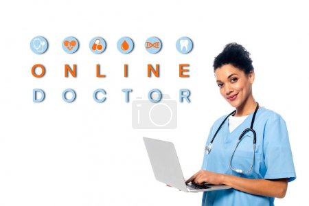 Photo for African american nurse with stethoscope and laptop smiling and looking at camera isolated on white, online doctor illustration - Royalty Free Image