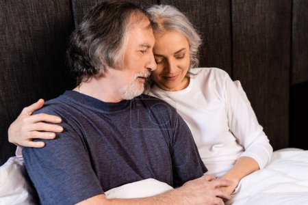 Photo for Happy mature couple hugging and smiling in bed - Royalty Free Image