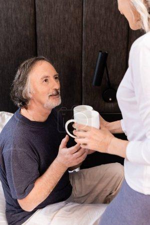 Photo pour Femme mature tenant des tasses avec des boissons près de mari d'âge moyen - image libre de droit