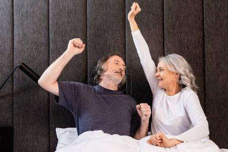 Photo pour Heureux mature homme et femme avec les mains au-dessus de la tête en se regardant dans la chambre - image libre de droit