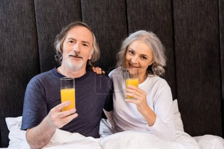 happy mature couple holding glasses with orange juice in bed