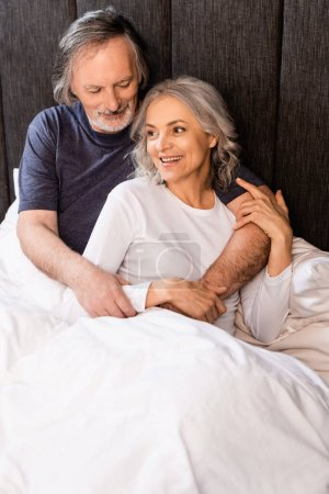 middle aged couple smiling and hugging in bed
