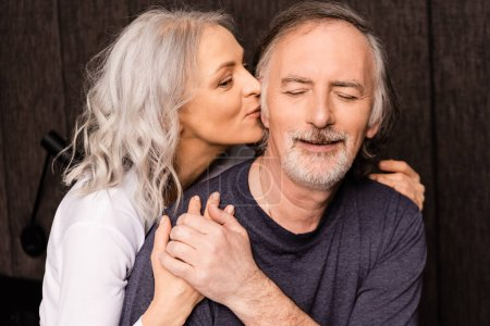 mature woman kissing cheek of happy husband with closed eyes