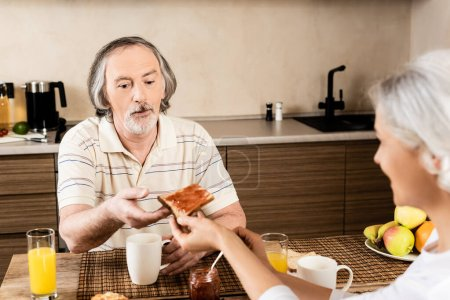 selective focus of mature woman giving sweet toast bread with jam to husband