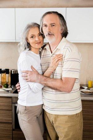 heureux couple d'âge moyen câlin dans la cuisine