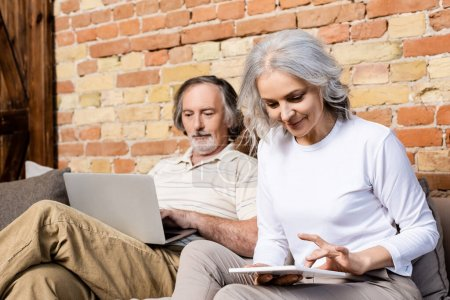Photo for Selective focus of happy mature woman using digital tablet near husband with laptop in living room - Royalty Free Image