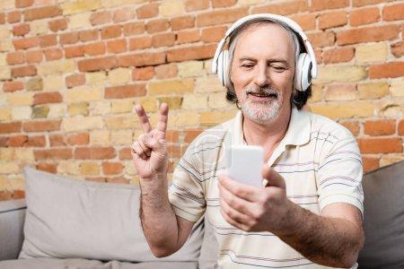 Photo pour Homme gai et mature dans les écouteurs sans fil prenant selfie et montrant signe de paix dans le salon - image libre de droit