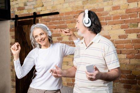 glückliche reife Frau in drahtlosen Kopfhörern tanzt neben Ehemann mit Smartphone