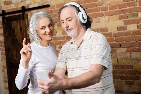 Photo pour Foyer sélectif de la femme mûre gaie dans les écouteurs sans fil pointant avec le doigt mari proche avec smartphone - image libre de droit