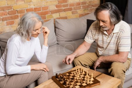 Photo for Mature man and woman playing chess in living room - Royalty Free Image