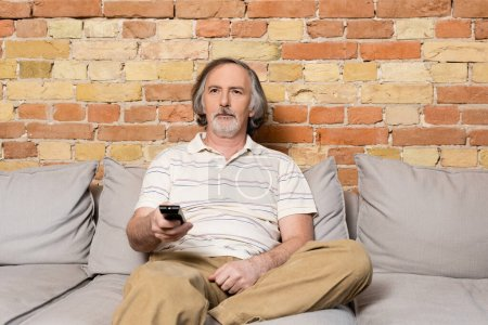 Photo pour Homme barbu et mature tenant télécommande tout en regardant un film à la maison - image libre de droit
