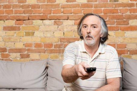 Photo pour Foyer sélectif de l'homme surpris et mature tenant télécommande tout en regardant un film à la maison - image libre de droit