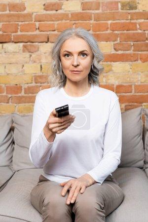 reife Frau hält Fernbedienung während Film zu Hause