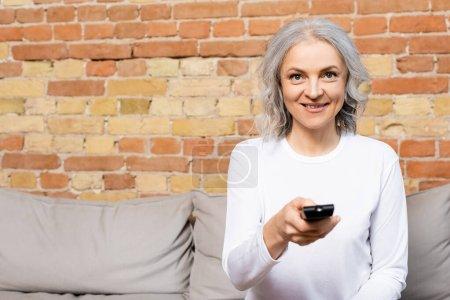 glückliche und reife Frau mit Fernbedienung, während sie Film zu Hause anschaut