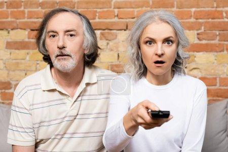 Photo pour Foyer sélectif de couple surpris et mature regarder un film dans le salon - image libre de droit