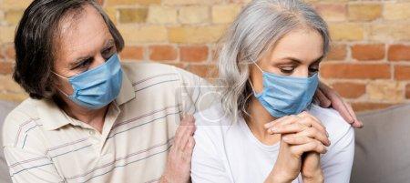 Photo pour Récolte horizontale de l'homme mature dans le masque médical toucher femme avec les mains serrées - image libre de droit