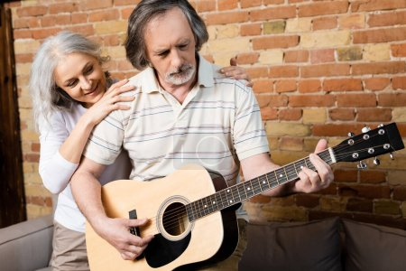 Photo for Bearded and mature man playing acoustic guitar near smiling wife - Royalty Free Image