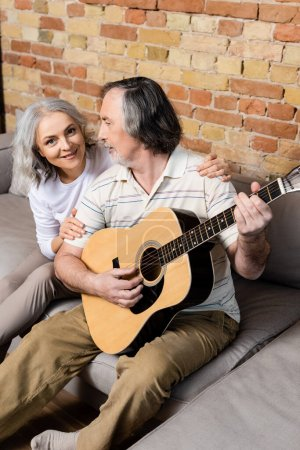 bearded and mature man playing acoustic guitar near cheerful wife
