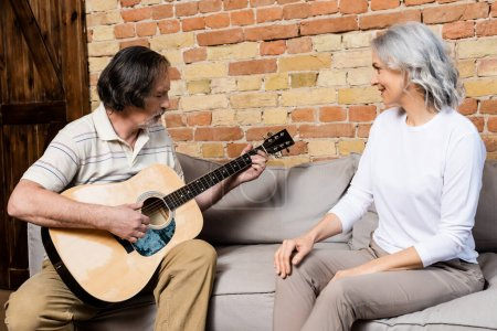 Photo for Bearded and mature man playing acoustic guitar near happy wife - Royalty Free Image