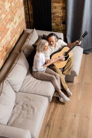 Photo pour Vue aérienne d'un homme barbu et mature jouant de la guitare acoustique près d'une femme joyeuse - image libre de droit
