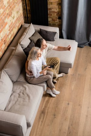 overhead view of middle aged couple watching movie in living room
