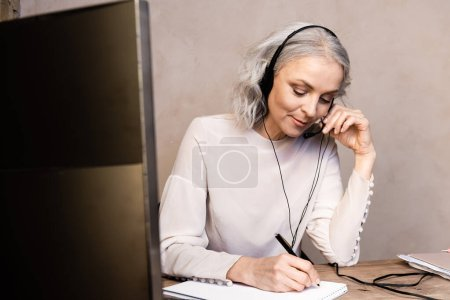 Photo for Selective focus of mature operator touching headset while writing in notebook near computer monitor at home - Royalty Free Image