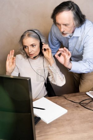 Photo for Selective focus of mature operator in headset talking near husband showing ok sign - Royalty Free Image