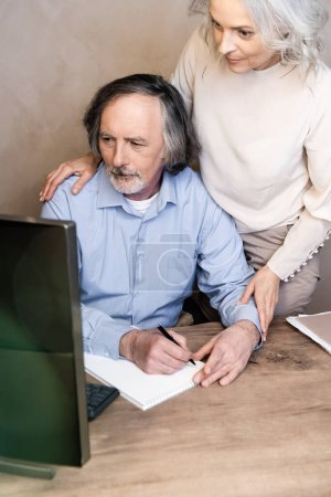 selective focus of mature man writing in notebook near wife and looking at computer monitor