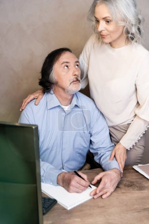 selective focus of mature man writing in notebook and looking at wife near computer monitor