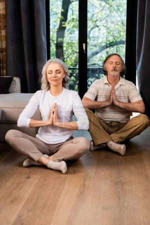 Photo pour Couple mature détendu avec les yeux fermés et les mains priantes assis dans la pose de lotus - image libre de droit