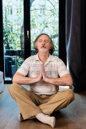 Photo pour Homme mûr détendu avec les yeux fermés et les mains priantes assis dans la pose du lotus - image libre de droit