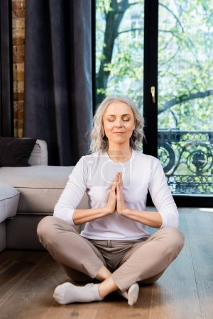 Photo for Relaxed mature woman with closed eyes and praying hands sitting in lotus pose - Royalty Free Image