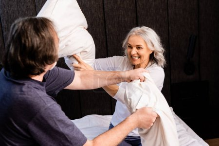 Photo for Selective focus of cheerful mature woman pillow fighting with husband in bedroom - Royalty Free Image