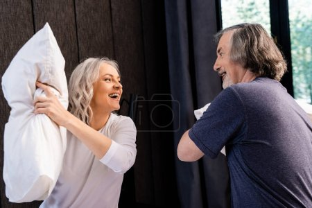 Photo pour Heureux couple mature oreiller combat dans chambre - image libre de droit