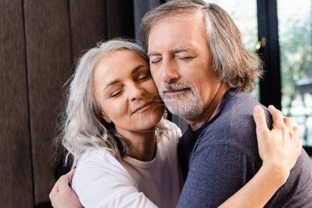 Photo pour Heureux couple d'âge moyen avec les yeux fermés étreignant à la maison - image libre de droit