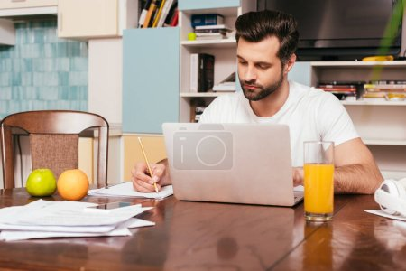 Photo for Selective focus of handsome freelancer working with papers and laptop near orange juice and fruits on table - Royalty Free Image