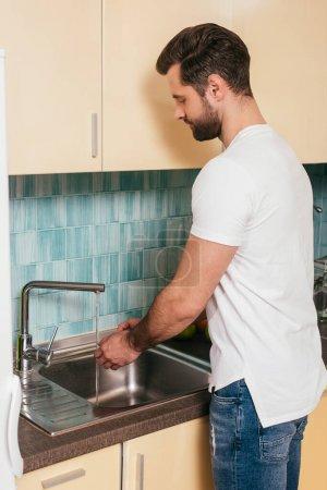 Photo pour Vue latérale d'un bel homme qui se lave les mains dans la cuisine - image libre de droit