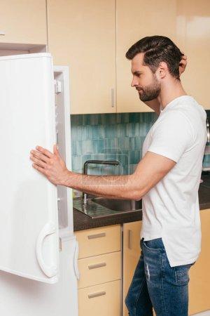 Photo pour Vue latérale d'un homme pensif regardant un réfrigérateur ouvert dans la cuisine - image libre de droit