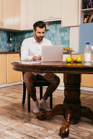 Photo pour Beau homme en chemise et culotte en utilisant un ordinateur portable près des fruits et du lait dans la cuisine - image libre de droit