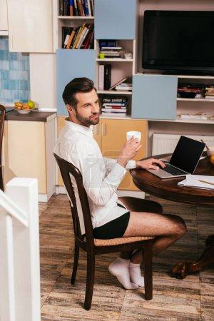 Photo pour Focus sélectif de bel homme en chemise et culotte à l'aide d'un ordinateur portable et tenant la tasse dans le salon - image libre de droit