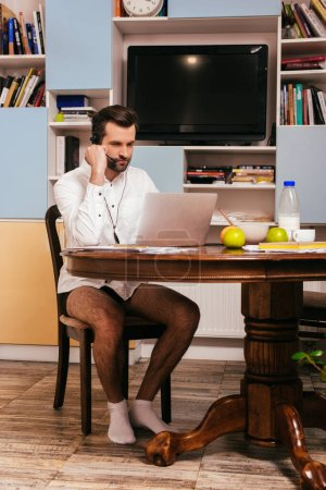 Freelancer in shirt and panties using headset and laptop near breakfast on kitchen table
