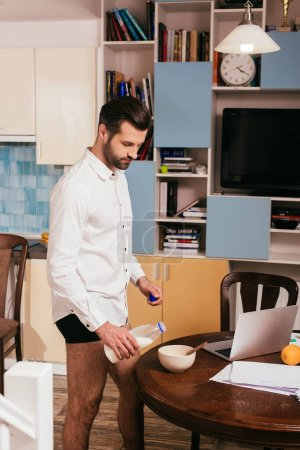 Photo for Side view of handsome man in panties and shirt pouring milk in bowl near laptop and papers on table - Royalty Free Image