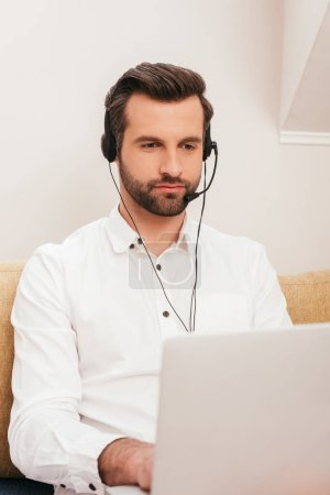 Selective focus of handsome teleworker using laptop and headset at home