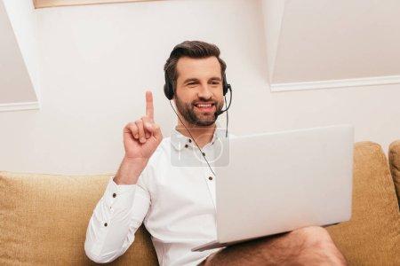 Photo pour Concentration sélective de sourire pigiste dans le casque ayant idée lors de l'appel vidéo sur ordinateur portable à la maison - image libre de droit