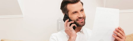 Photo for Handsome teleworker smiling while talking on smartphone and holding document at home, panoramic crop - Royalty Free Image