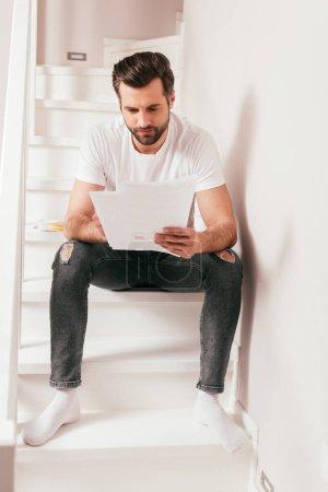 Photo pour Beau pigiste qui travaille avec des papiers dans les escaliers de la maison - image libre de droit