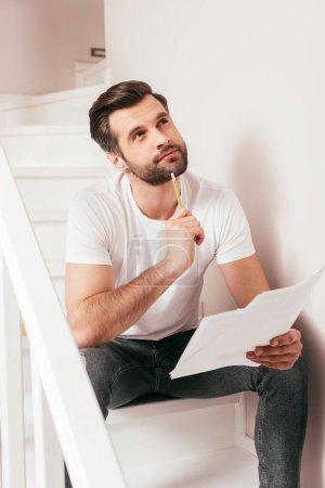 Photo pour Télétravailleur rêveur regardant loin tout en tenant des papiers et un crayon sur les escaliers - image libre de droit