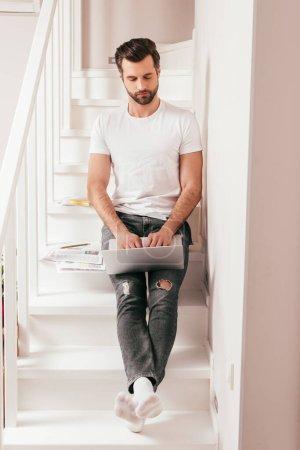 Photo pour Beau télétravailleur utilisant un ordinateur portable près des papiers sur les escaliers - image libre de droit